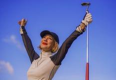 Jeune augmenter de sourire de belle et heureuse de golf femme de joueur arme dans le signe de victoire organisant le club et le t photos stock