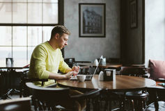 Jeune auteur dans un café confortable Images libres de droits