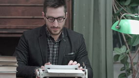 Jeune auteur en verres frottant ses mains et commençant la dactylographie sur une machine à écrire rouge de vintage banque de vidéos