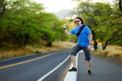 Jeune auto-stop de touristes le long d'une route Image libre de droits