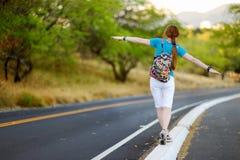 Jeune auto-stop de touristes le long d'une route Photo stock