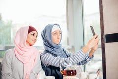 Jeune autoportrait musulman heureux de prise de la femme deux avec le handphone au café Image stock