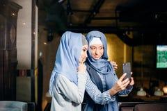 Jeune autoportrait musulman heureux de prise de la femme deux avec le handphone au café Photo stock