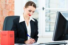 Avocat dans le bureau faisant des notes dans un dossier Image stock