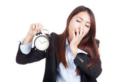 Jeune bâillement asiatique de femme d'affaires avec le réveil Photographie stock libre de droits