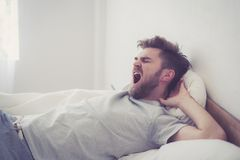 Jeune bâillement masculin américain beau dormant dans le lit à la maison photo stock