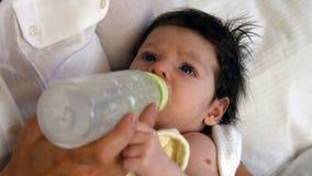 Jeune bébé buvant d'une bouteille à lait banque de vidéos