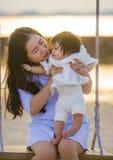 Jeune bébé chinois asiatique doux et heureux de participation de femme balançant ensemble à l'oscillation de plage sur le coucher photo stock