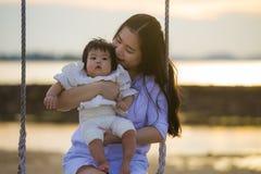 Jeune bébé chinois asiatique doux et heureux de participation de femme balançant ensemble à l'oscillation de plage sur le coucher photographie stock