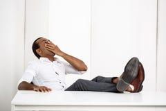 Jeune baîllement africain réussi somnolent d'homme d'affaires, se reposant sur le lieu de travail Photo libre de droits