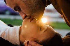 Jeune baiser de couples dans des faisceaux du soleil Photos stock