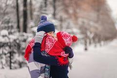 Jeune baiser heureux de couples et dissimulation derrière une écharpe rouge en parc d'hiver Photo libre de droits