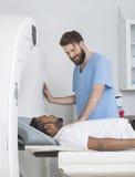 Jeune balayage de docteur About To Start CT sur le patient masculin Image libre de droits