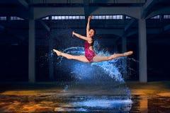 Jeune ballerine avec l'éclaboussure de l'eau dans la synchronisation à grande vitesse photo stock