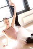 Jeune ballerine dans l'étirage rose en Sunny Studio Image stock