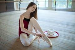 Jeune ballerine s'asseyant sur la salle de classe de danse de plancher Photographie stock