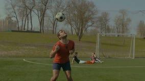 Jeune ballon de football de titre de footballer sur le champ banque de vidéos