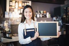 Jeune barman asiatique de femmes tenant le menu vide de tableau dans le coffe Photos stock