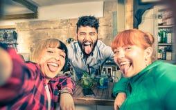 Jeune barman beau flirtant avec de belles filles à la barre Images libres de droits
