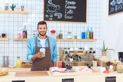 jeune barman beau tenant le latte dans la tasse en plastique et le sourire photos stock
