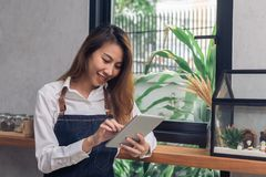 Jeune barman femelle asiatique utilisant le comprimé électronique dans son propre café tout en takeing la coupure dans l'après-mi Photos stock