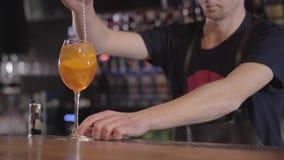 Jeune barman mélangeant un cocktail régénérateur de whiskey ou d'alcool en verre à de la glace Fin vers le haut clips vidéos