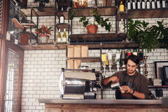Jeune barman masculin faisant une tasse du café image libre de droits