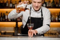 Jeune barman versant la boisson alcoolisée dans un verre Images stock