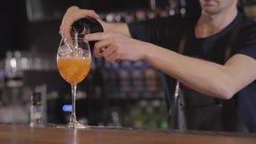 Jeune barman versant un cocktail régénérateur de whiskey ou d'alcool dans un verre avec de la glace Fin vers le haut banque de vidéos