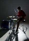 Jeune batteur jouant dans la lumière de contre Photographie stock