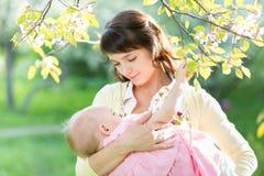 Jeune bébé d'allaitement au sein de mère dans le jardin Image libre de droits