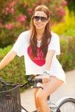 Jeune beau bicicle d'équitation de femme l'été Image libre de droits