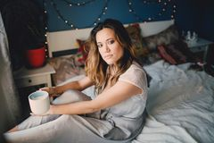Jeune beau café de boissons de femme à la maison se trouvant sur le lit Photos stock