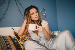 Jeune beau café de boissons de femme à la maison se trouvant sur le lit Image libre de droits