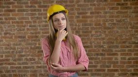 Jeune beau constructeur de fille tenant et évaluant quelque chose, processus de pensée, fond de brique clips vidéos
