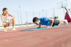 Jeune, beau, convenable et en bonne santé entraîneur personnel comptant la poussée Photographie stock