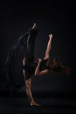Jeune beau danseur dans la danse beige de robe sur le fond noir photos libres de droits