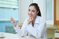 Jeune beau dentiste de femme tenant les outils dentaires photo stock