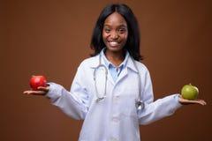 Jeune beau docteur africain de femme de zoulou contre le backgrou brun image stock