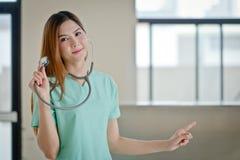 Jeune beau docteur féminin de sourire heureux montrant le secteur vide f Image libre de droits