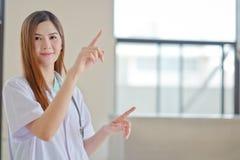 Jeune beau docteur féminin de sourire heureux montrant le secteur vide f Photo libre de droits