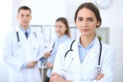 Jeune beau docteur féminin souriant sur le fond avec le patient dans l'hôpital photographie stock