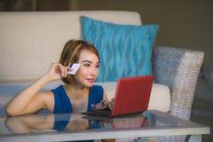 Jeune beau et heureux salon de femme à la maison tenant la carte de crédit utilisant l'ordinateur portable pour les banques et le photo stock