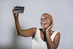 Jeune beau et heureux sourire afro-américain noir de femme excité prenant le portrait de photo de selfie avec le téléphone portab photographie stock libre de droits
