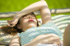 Jeune beau et sexy mensonge coréen asiatique de femme confortable au lit de jardin de station de vacances de vacances ayant le br image stock