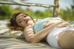 Jeune beau et sexy mensonge coréen asiatique de femme confortable au lit de jardin de station de vacances de vacances ayant le br photos libres de droits