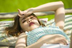 Jeune beau et sexy mensonge coréen asiatique de femme confortable au lit de jardin de station de vacances de vacances ayant le br photo stock