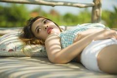 Jeune beau et sexy mensonge coréen asiatique de femme confortable au lit de jardin de station de vacances de vacances ayant le br photo libre de droits