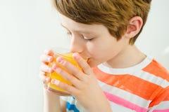 Jeune beau garçon caucasien buvant du jus d'orange du verre photos libres de droits