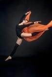 Jeune beau gymnaste d'athlète de femme dans le mouvement sur le backgro noir Photos stock
